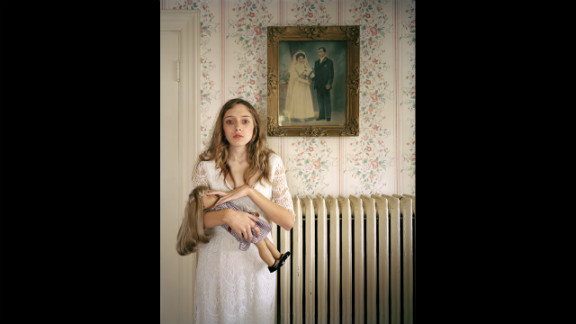 Third prize people -- observed portraits single: Kayla with a lookalike doll in front of a portrait of her ancestors in Boston.