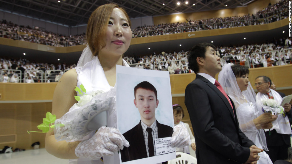 Mongolian bride Baatar Chuluun holds her groom's picture during the mass ceremony.