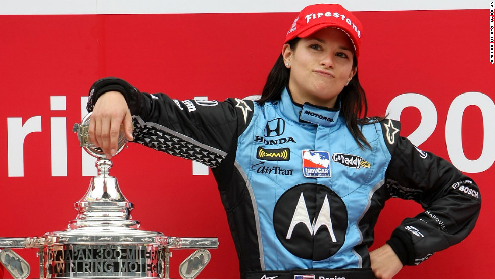 Here she poses with the trophy after winning the Bridgestone Indy Japan 300 Mile in 2008 in Japan, making her the first woman in history to win an IndyCar race.