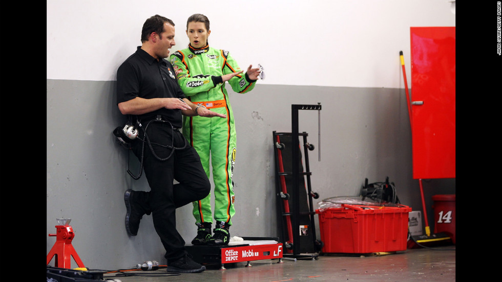 Patrick speaks to a crew member in the garage at Daytona International Speedway in 2012.