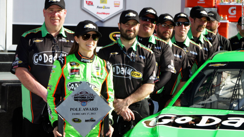 The 33-year-old holds the trophy with her crew after winning the pole award for the NASCAR Sprint Cup Series Daytona 500 in February 2013, again making her the first woman to do so.
