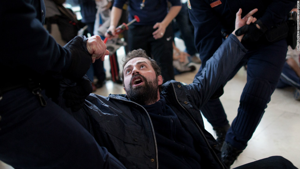Riot police pull at a worker protesting from Spanish Airline Iberia during a rally against job cuts at Barajas Airport.