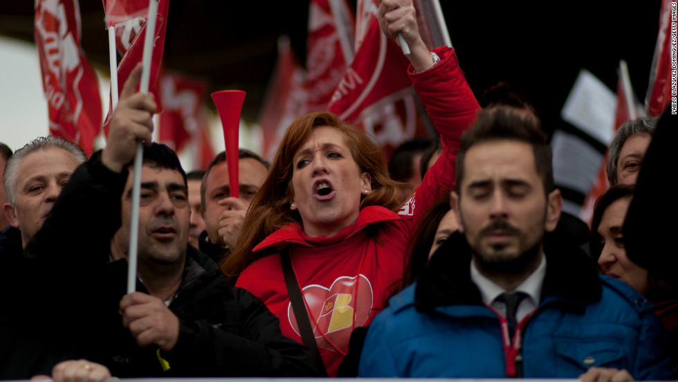 Staff from Spanish Airline Iberia hold flags and gather in protest against job cuts.