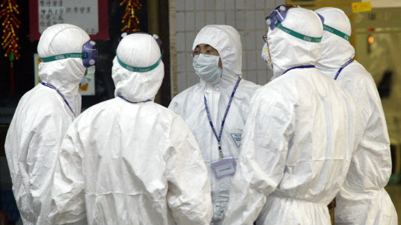 Health workers stand outside Block E of Amoy Gardens on April 8, 2003 in Hong Kong.