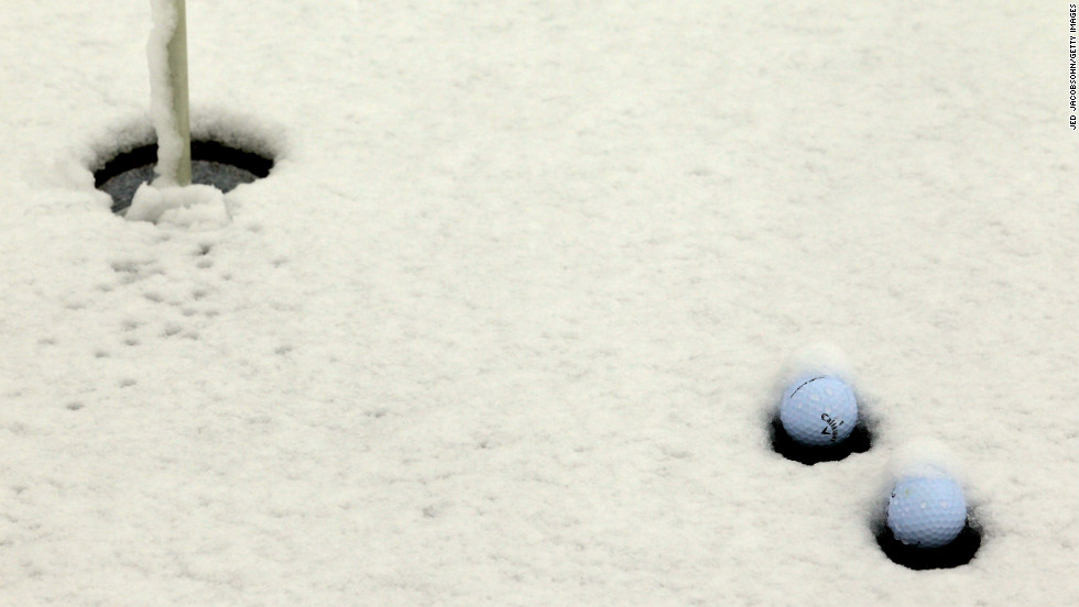Snow collects around golf balls on the practice putting green on Wednesday.