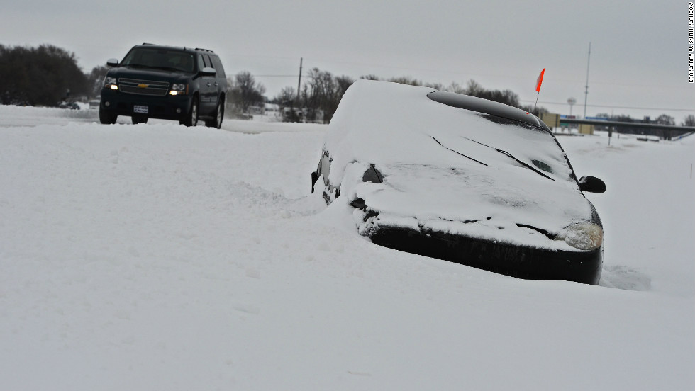 A car is stranded in the snow on Highway 135 outside Wichita, Kansas, on Thursday, February 21.