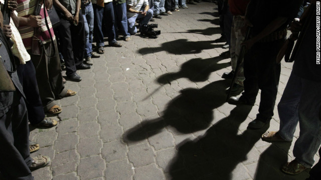 (File photo) Men stand guard while passing the detainees to the Government of the State of Guerrero on February 8, 2013.