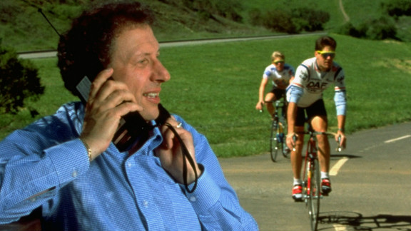 It's no iPhone. In this image from 1989, Allan Z. Loren, then-president of Apple Computer USA, talks on a mobile phone as cyclists ride past.