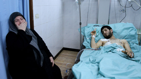 A woman sits by the hospital bed of a man allegedly injured when an armed group seized rooftops in Latakia on March 27, 2011, and opened fire at passers-by, citizens and security forces personnel according to official sources.