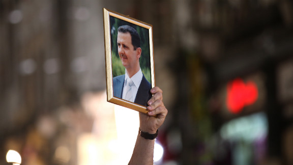 A Syrian man holds up a portrait of President Bashar al-Assad during a rally to show support for the president in Damascus on April 30, 2011.