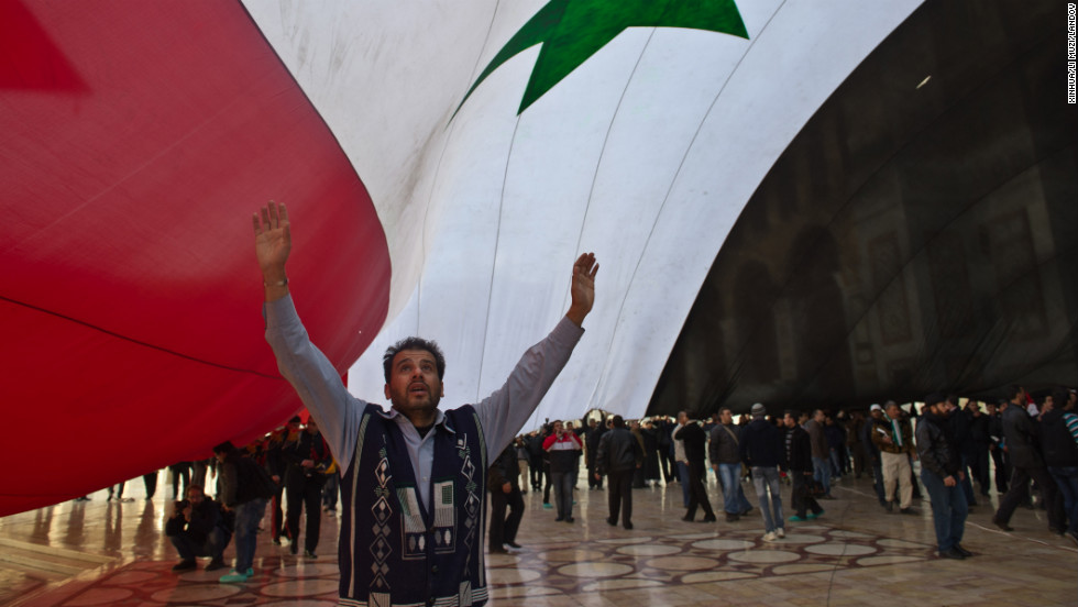 A man stands under a giant Syrian flag outside the Umayyad Mosque in Damascus on December 24, 2011.