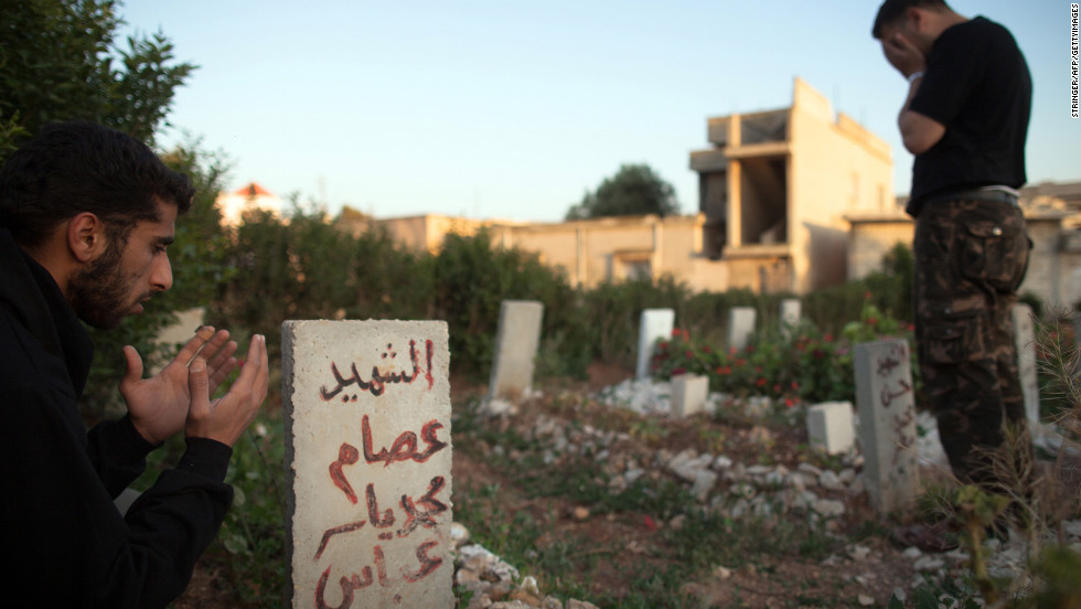 Members of the Free Syrian Army's Mugaweer (commandos) Brigade pay their respects in a cemetery on May 12, 2012 in Qusayr.