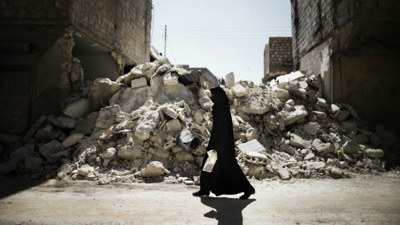 A woman walks past a destroyed building in Aleppo on September 13, 2012.