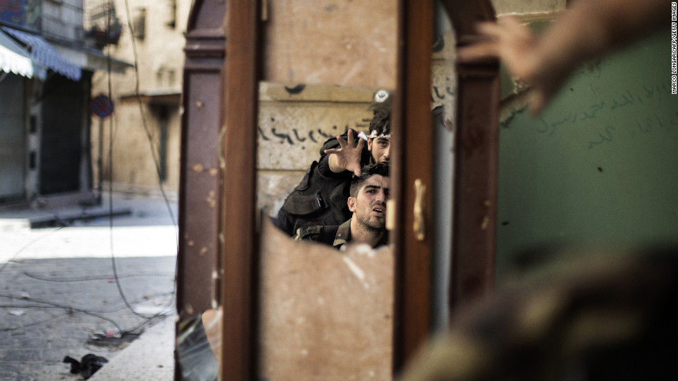 Free Syria Army fighters are reflected in a mirror they use to see a Syrian Army post only 50 meters away in Aleppo on September 16.
