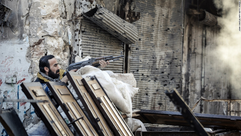 A rebel fighter fires at a Syrian government position in Aleppo on November 6, 2012.