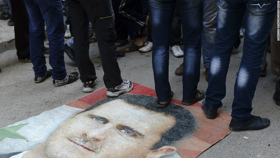 Syrians protesters stand on Assad's portrait during an anti-regime demonstration in Aleppo on November 16.