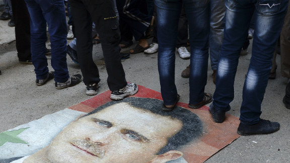 Syrians protesters stand on Assad