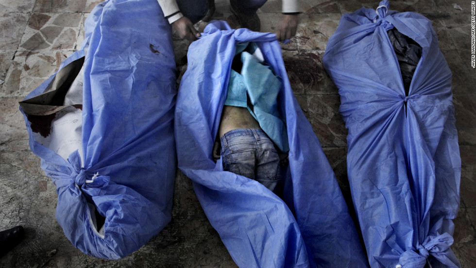 The bodies of three children, who were allegedly killed in a mortar shell attack that landed close to a bakery in Aleppo, on December 2, 2012, are laid out for identification by family members at a makeshift hospital at an undisclosed location of the city.