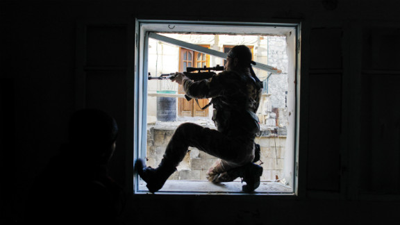 A member of Liwa Salahadin aims at a regime fighter in the besieged district of Karmel al-Jabl in Aleppo on December 6, 2012.