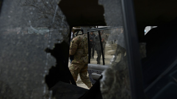 A US soldier and Afghan policemen are seen through the broken window of a suicide bombers