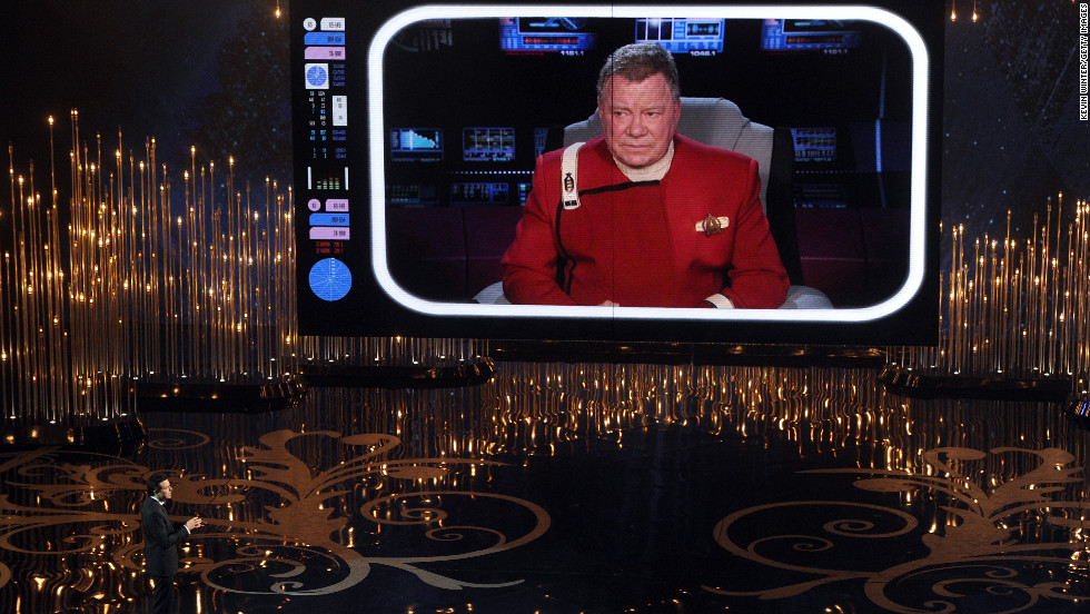 "MacFarlane talks to William Shatner on the video screen during his opening. Shatner gives the host tips to make sure tomorrow's headlines don't read ""worst Oscar host ever."""