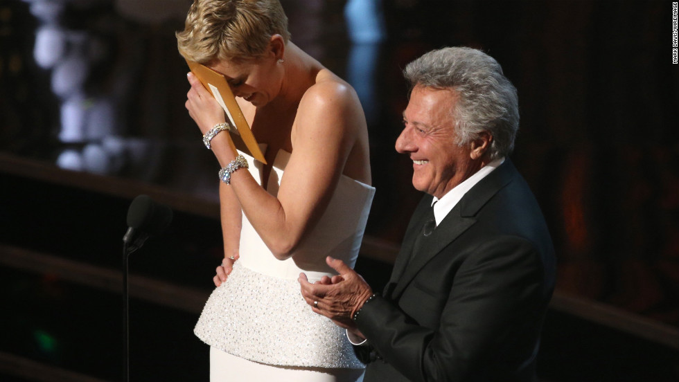 Charlize Theron blushes after Dustin Hoffman complimented her dance skills.