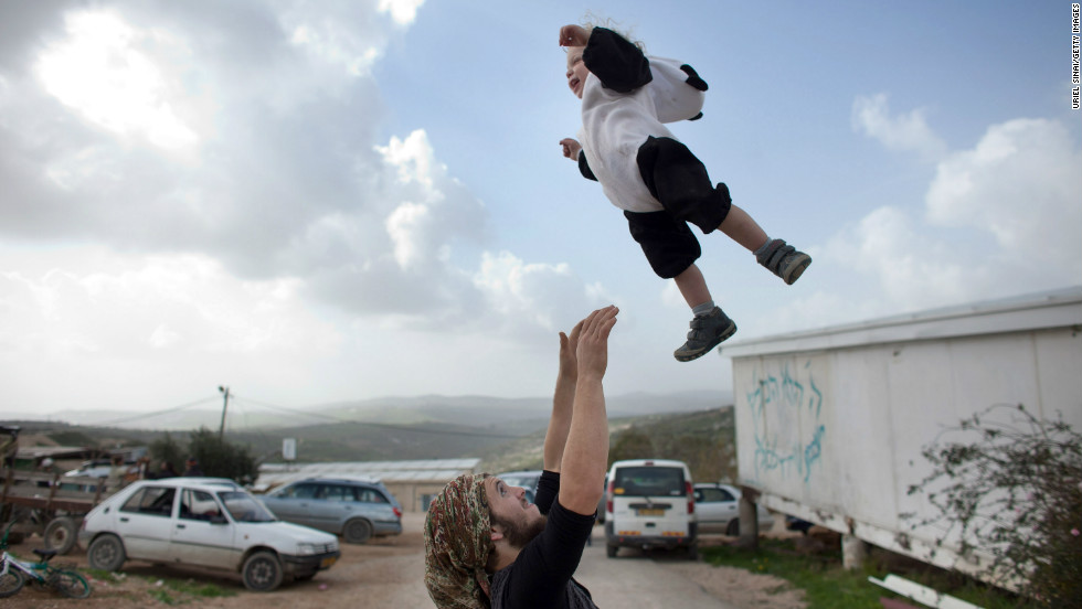 A Jewish settler plays with his baby at the settlement outpost of Havat Gilad, West Bank.