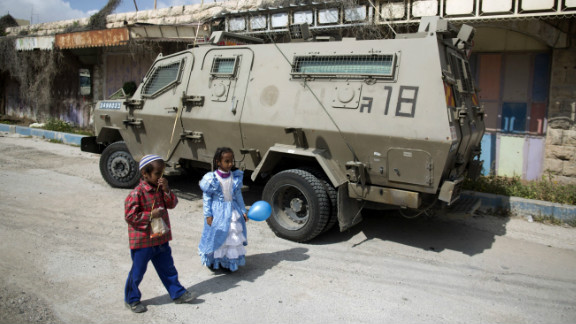 Children of Israeli settlers wearing costumes walk past an army vehicle as they celebrate the annual Purim parade in the occupied West Bank city of Hebron.
