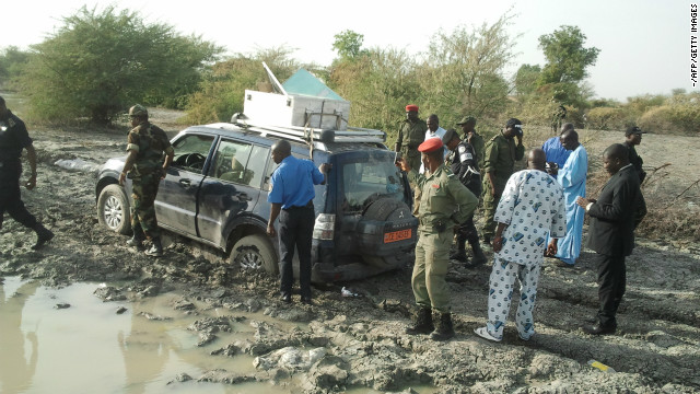 Cameroonian security officials stand at the vehicle a French family was driving before being kidnapped.