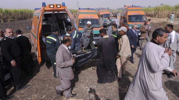 A body gets loaded onto an ambulance.