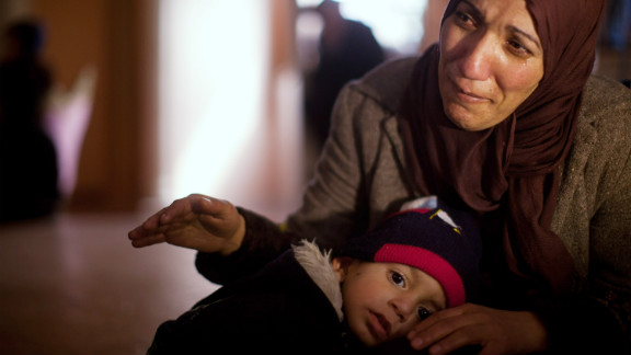 The sister of of Arafat Jaradat mourns, while holding his son Muhannad, during his funeral on February 25, 2013 in the village of Saair in the West Bank.