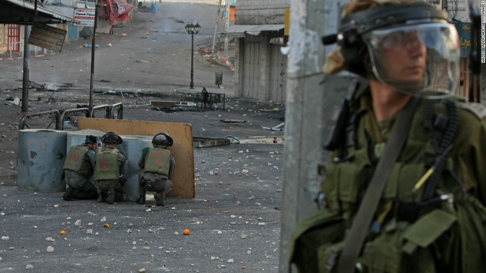 Israeli security forces take cover behind barrels during clashes with Palestinian protestors near the Israeli checkpoint in the West Bank town of Hebron on February 25, 2013.