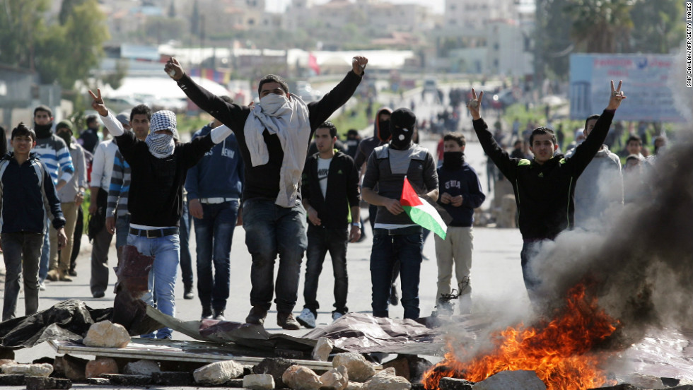 A Palestinian protestor holds his national flag as others flash the sign for victory during clashes with Israeli security forces at the entrance of the Jalama checkpoint, near the West Bank city of Jenin, on February 26, 2013.