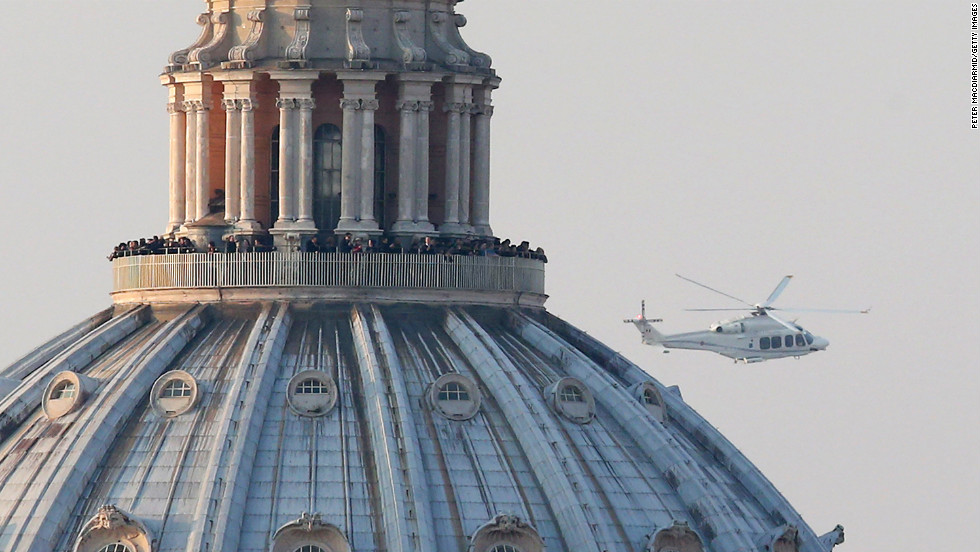 People crowd the gallery on top of St. Peter's Basilica as a helicopter carrying Pope Benedict XVI passes by on its way out of Vatican City.