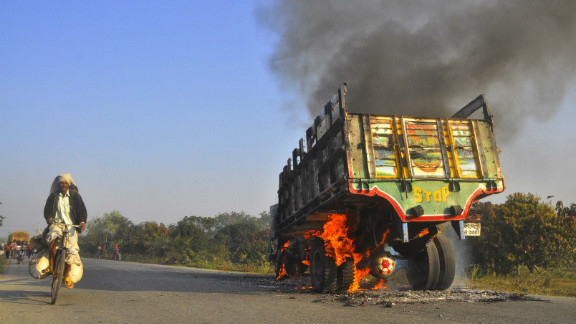 A man rides a bicycle past a bus set on fire during a clash with Jamaat-e-Islami activists in Rajshahi on February 28.