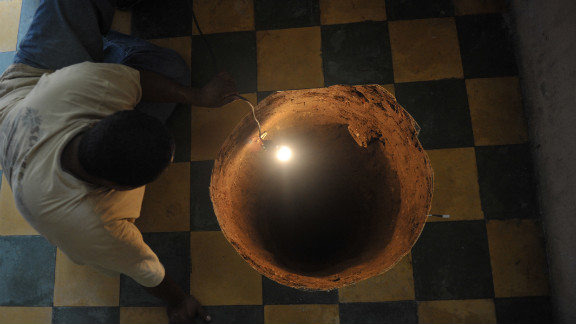 In July 2011, a man inspects a 40-foot-deep sinkhole that a family found after they heard a booming noise in their kitchen in Guatemala City, Guatemala.