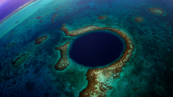 """The Great Blue Hole"" is the name of a massive underwater sinkhole off the coast of Belize. The deeper you go, the clearer the water becomes, revealing amazing stalactites and limestone."