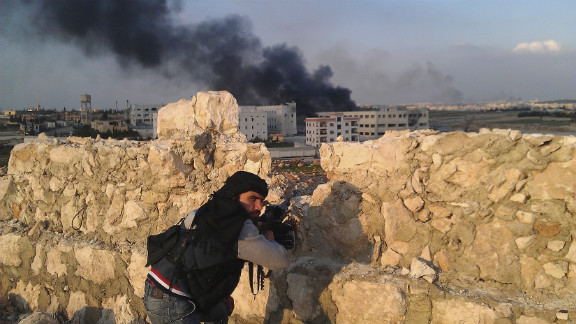 A Free Syrian Army fighter looks back as smoke rises during fighting between rebel fighters and forces loyal to Syria