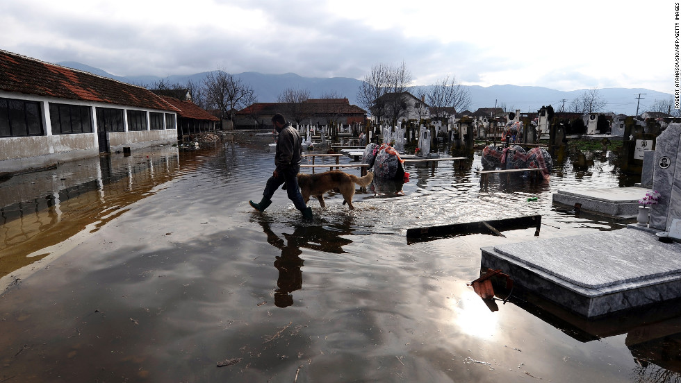 A man and a dog cross the flooded graveyard in the village of Monospitovo, Macedonia, on February 27. Torrential rains poured down on the Strumica Valley, destroying or damaging crops and households.