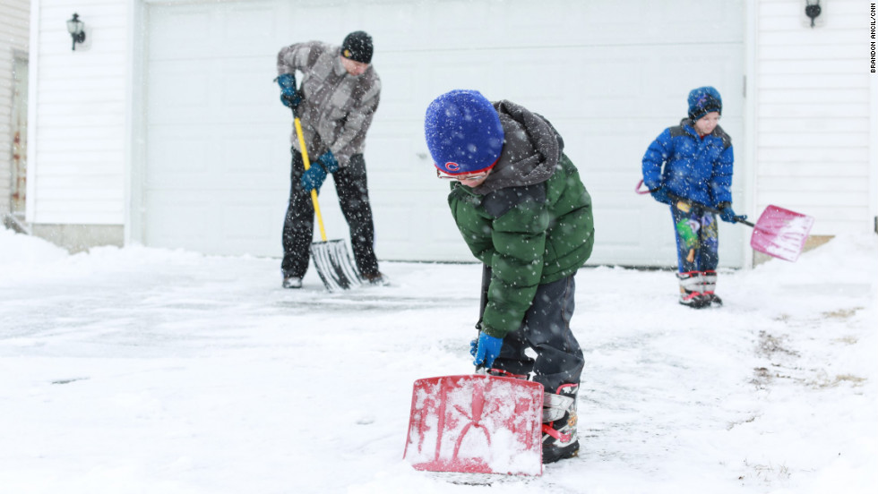 Left to right: Anthony Jordan and his 6-year-old twin sons Griffin and Landin shovel their driveway in Sycamore, Illinois, on March 5.