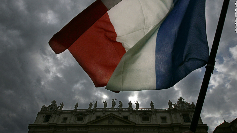 A French flag is waved in front of St. Peter's as white smoke billows from the chimney of the Sistine Chapel to announce the election of a new pope after a conclave lasting little more than 24 hours, on April 19, 2005.