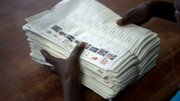 A voting assistant stacks ballot papers marked with a vote for presidential candidate Raila Odinga to an assistant at the Olympic Primary School in Kibera, Nairobi on March 4, 2013.