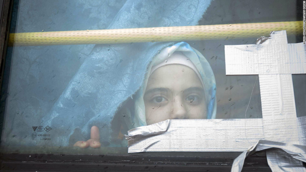A Syrian girl looks through the window of a bus where she has lived with her family for the past eight months in February 2013.