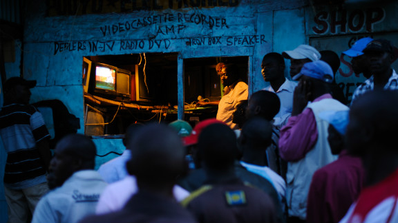 Men watch the incoming provisional election results on a television outside a shop in the Kibera slum of Nairobi, Kenya