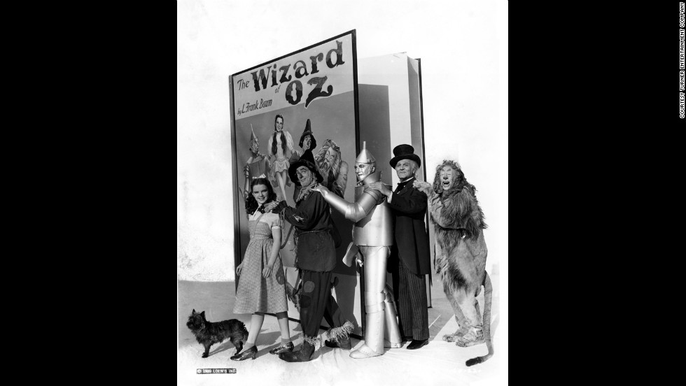 "Judy Garland as Dorothy Gale, Ray Bolger as the Scarecrow, Jack Haley as the Tin Man, Frank Morgan as the Wizard, Bert Lahr as the Cowardly Lion and Terry as Toto with an oversized prop book of ""The Wizard of Oz."""