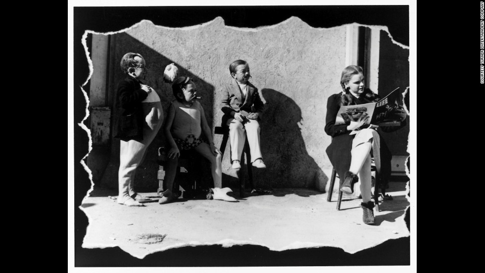 Judy Garland reads a copy of Life magazine on set as three of the actors playing Munchkins stand by.