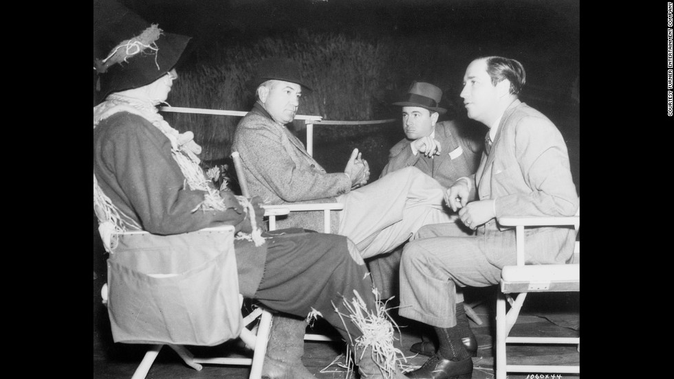 Ray Bolger in costume as the Scarecrow, seated with director Victor Fleming, choreographer Bobby Connolly and producer Mervyn LeRoy.