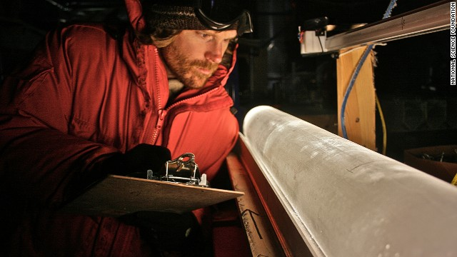 A scientist looks at an ice core from the West Antarctic Ice Sheet Divide coring site.