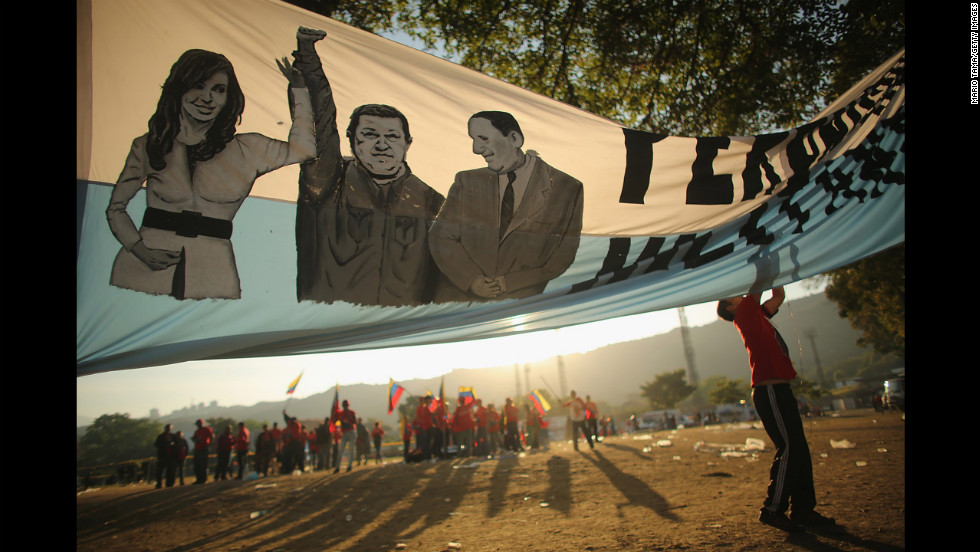 A man adjusts a banner before the start of Venezuelan President Hugo Chavez's funeral outside the Military Academy on Friday, March 8, in Caracas.  Uncertainty swirled around what happens next in Venezuela as the deeply divided South American country mourned its late leader. Chavez, 58, died Tuesday, March 5, after a battle with cancer.