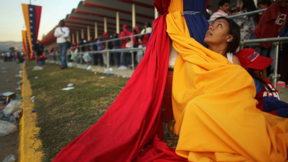 A woman wraps up in Venezuela's flag to stay warm as she and others wait in line before the start of Chavez's funeral on March 8 in the capital.